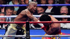 Mayweather throws a punch at Pacquiao during their
