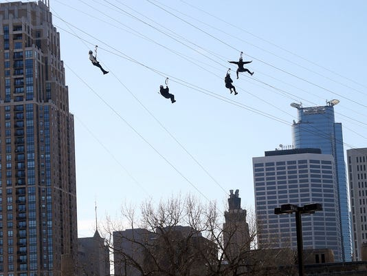 Zipline enthusiasts including politicians, celebrities and media cross the Mississippi River in Minneapolis Friday, Jan. 26, 2018 as the 10-day Bold North theme festival got underway, one of many events leading up to the Super Bowl. (AP Photo/Jim Mone)