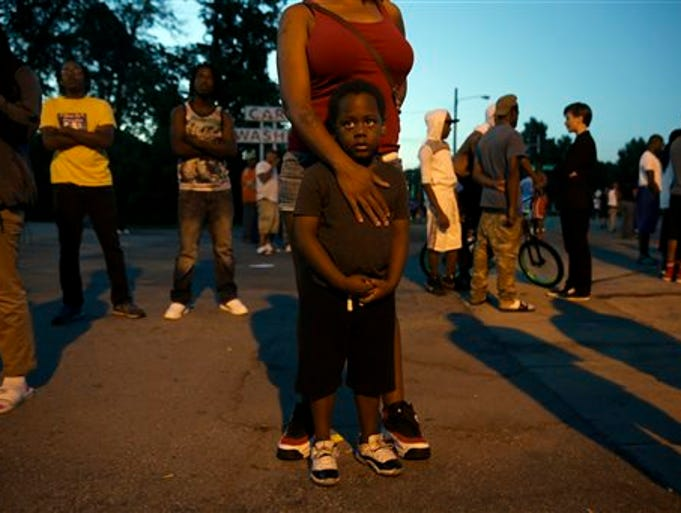 Jeremiah Parker, 4, stands in front of his mother, Shatara Parker, as they attend a protest Wednesday, Aug. 13, 2014, in Ferguson, Mo. Nights of unrest have vied with calls for calm in a St. Louis suburb where Michael Brown, an unarmed black teenager was killed by police, while the community is still pressing for answers about the weekend shooting. (AP Photo/Jeff Roberson)