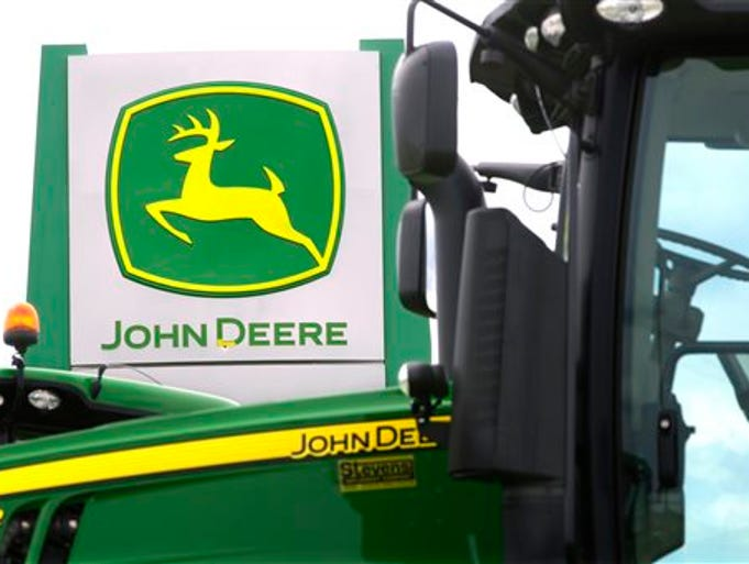 This Sunday, June 8, 2014 photo shows John Deere farming equipment at a dealership in Petersburg, Ill. John Deere's third-quarter profit fell 15 percent and the farming equipment maker believes that the same weak sales at home and abroad will cut into earnings for the entire year.