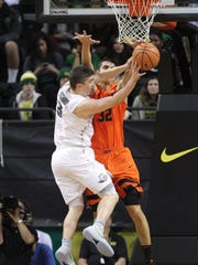 Oregon's Payton Pritchard (3) passes the around Oregon State's Seth Berger.