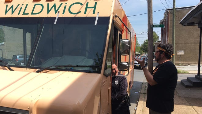 Mike Stanley, WiLDWiCH's owner, speaks to a Wilmington officer investigating the recovered food truck.