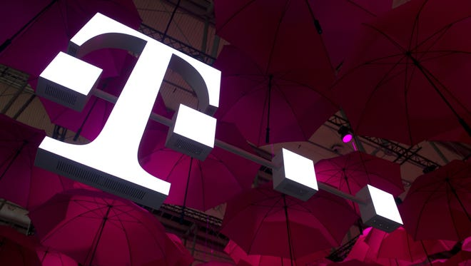 A Deutsche Telekom T-Mobile logo hangs under pink umbrellas at the stand of the German telecommunications giant at the 2014 CeBIT computer technology trade fair on March 10, 2014 in Hanover, central Germany.