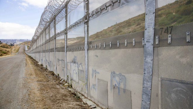 A section of pedestrian fencing along the U.S.-Mexico border fence in San Diego uses mesh and razor wire.