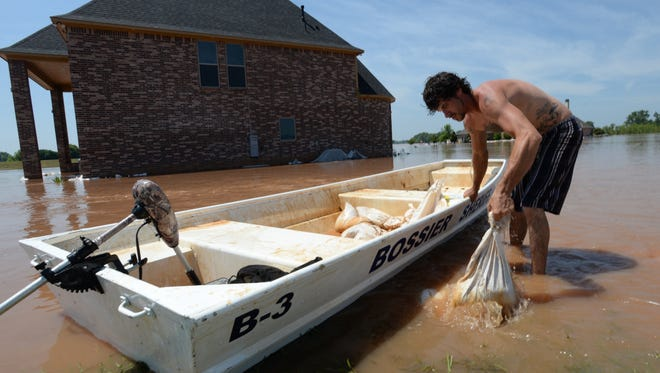 Codey Burnett loads a Bossier Sheriffs office boat with sandbags while working in the River Bluff subdivision.