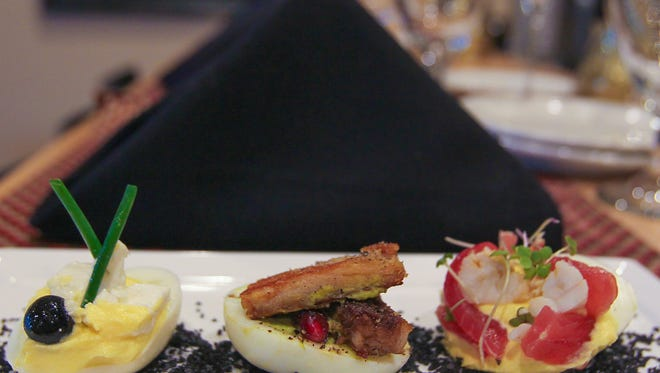 """A sampling of Chef Harold Balink's creations at Harold's in south Fort Myers: from left,  a roasted butternut squash deviled egg with Australian feta, blueberry and chives; """"Green Eggs and Ham"""", a cilantro and spinach deviled egg with pork belly and pomegranate seeds; and a ginger deviled egg with blue crab, tuna and wasabi greens."""