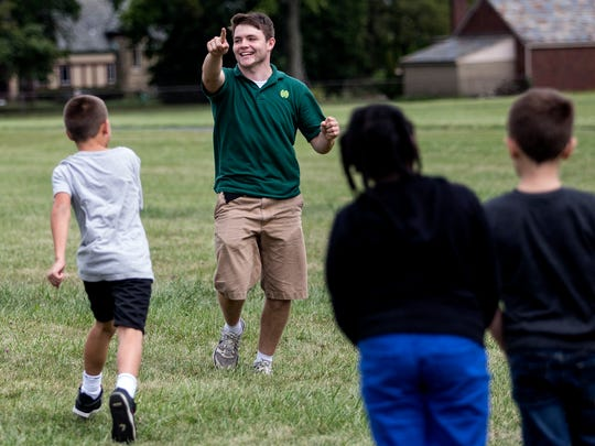 Jim Lally, a student at Newark Catholic, plays a game of kickball with students from McGuffey Elementary School. Students from Newark Catholic have been walking over to the elementary school to lead the kids in games during recess.