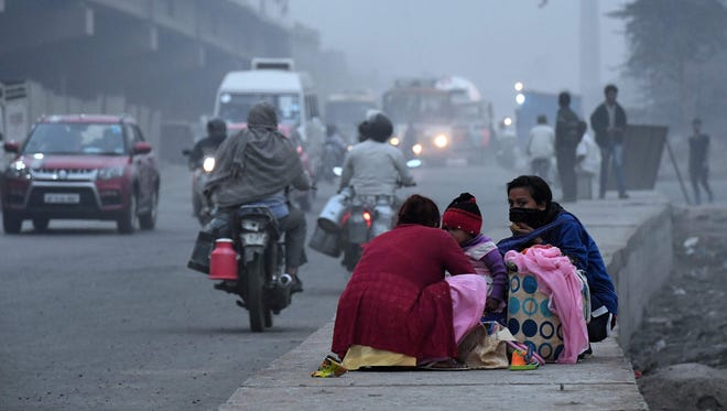 An Indian family waits for transportion by a roadside shrouded in smog in New Delhi on October 31, 2017.