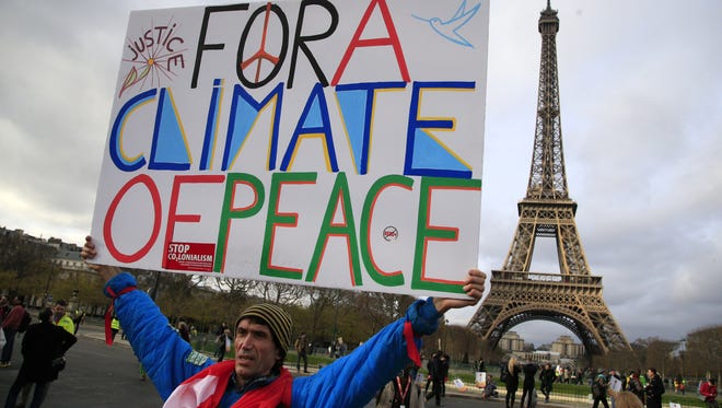 An activist hold a poster during a demonstration near the Eiffel Tower, in Paris during the COP21, the United Nations Climate Change Conference.