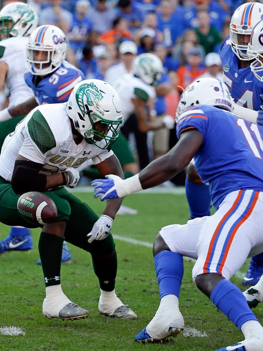 UAB running back Spencer Brown, left, fumbles the ball in front of Florida linebacker Vosean Joseph (11) during the first half of an NCAA college football game, Saturday, Nov. 18, 2017, in Gainesville, Fla. Florida recovered the fumble. (AP Photo/John Raoux)