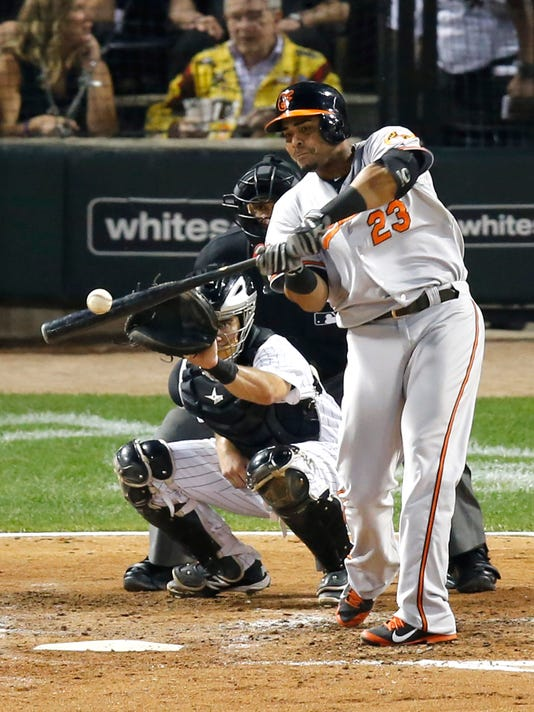 Baltimore Orioles' Nelson Cruz hits a two-run home run off Chicago White Sox starting pitcher Hector Noesi, also scoring Adam Jones, during the fourth inning of a baseball game Wednesday, Aug. 20, 2014, in Chicago. Watching the play behind the plate are catcher Adrian Nieto and umpire Eric Cooper. (AP Photo/Charles Rex Arbogast)
