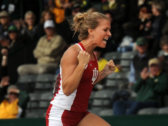 FILE – Kelsie Ahbe, of Indiana, celebrates after clearing the bar in the women's pole vault at the NCAA Track and Field Championships, June 13, 2014, in Eugene, Ore.