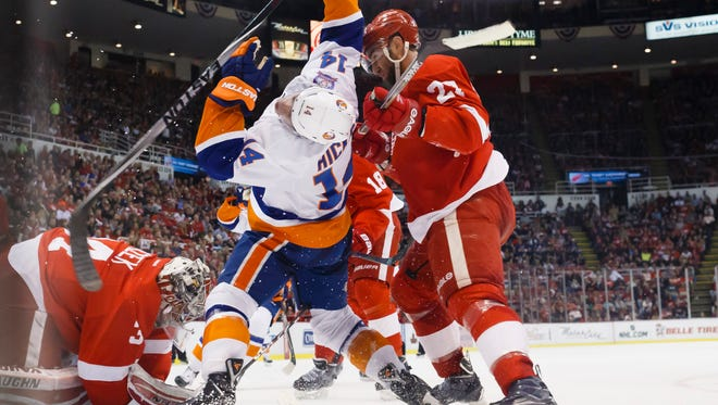 Detroit Red Wings defenseman Kyle Quincey and New York Islanders defenseman Thomas Hickey fight for position with in front of Detroit goalie Petr Mrazek in the second period at Joe Louis Arena.