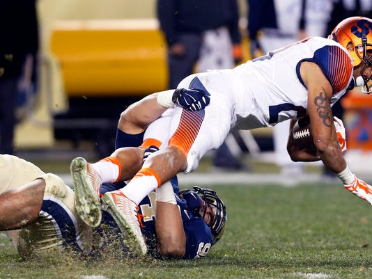 Syracuse running back George Morris II, right, is tackled by Pittsburgh defensive lineman Jeremiah Taleni (94) in the fourth quarter of an NCAA college football game, Saturday, Nov. 22, 2014, in Pittsburgh. Pittsburgh won 30-7. (AP Photo/Keith Srakocic)