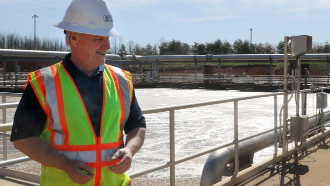 "Clarksville Gas and Water general manager Pat Hickey stands near water being purified by microorganisms or ""bugs"" and aeriated at the waste water treatment facility. The water in the tank is so oxygenated a person would sink to the bottom if they fell in according to Hickey."
