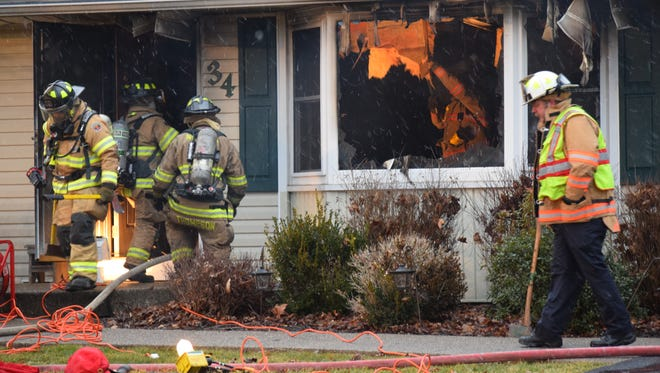 Crews work to eliminate hot spots in the house that caught fire Thursday evening.