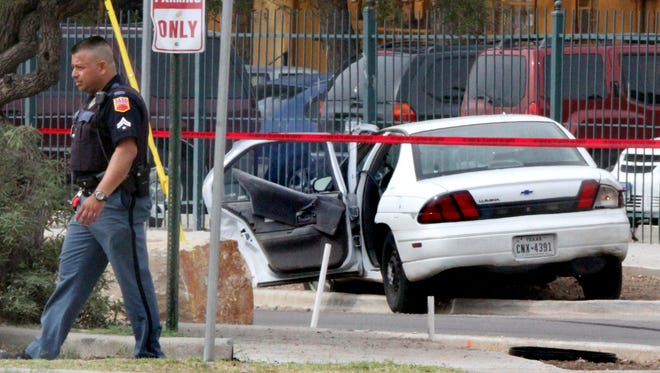 An El Paso police officer crosses Kernel Circle near a white Chevy Lumina that possibley was involved in a police relatede shooting incident Monday in El Paso's Lower Valley.