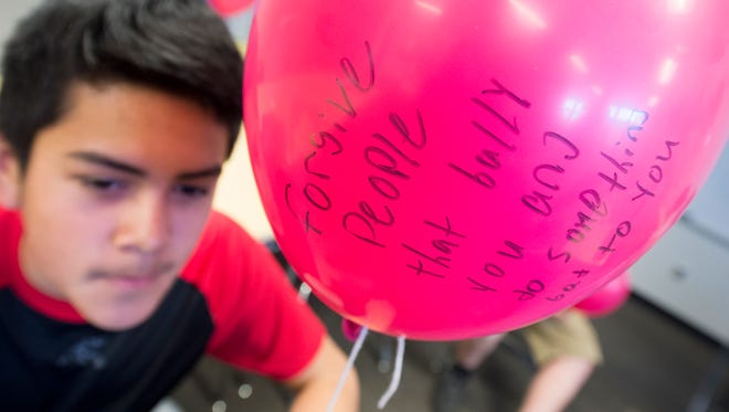 Jose Mendez, a seventh grader, wrote a message forgiving bullies on a pink balloon. Northeastern Middle School released balloons to honor Hope Westrick, a former student who died from cancer in December.