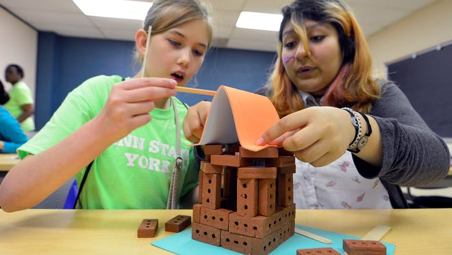Grace Dubs, 12 at left, and Dayanna Garibay, 13, from STEAM Academy build a structure from small bricks during the annual Penn State York Explore STEM event, Friday May 13, 2016. Each structure had to meet height requirements and pass snow (weight) wind and earthquake tests.John A. Pavoncello photo