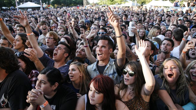Music fans cheer on Circa Survive Tuesday, July 8, 2014, on the opening night of the Common Ground Music Festival at Louis Adado Riverfront Park in downtown Lansing.    [Photo July 8, 2014 by MATTHEW DAE SMITH   for the Lansing State Journal]