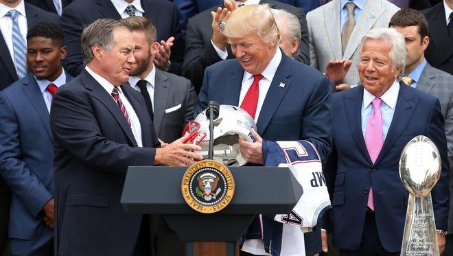New England Patriots head coach Bill Belichick presents President Donald Trump with a Super Bowl LI team helmet at a ceremony honoring the Super Bowl LI champion Patriots.