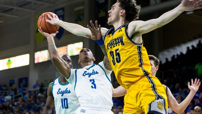 Florida Gulf Coast University sophomore, Rayjon Tucker, #3, goes for a layup against Kennesaw State University freshman, Zach Cameron, #35, during their game on Saturday, February 11, 2017 at Alico Arena in Estero.