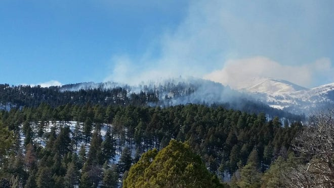 Smoke from a prescribed burn in the Lincoln National Forest floats above the trees..