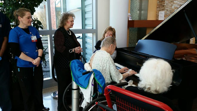 Family members, church congregants and hospital staff listen March 31, 2016 as Harry Lawson plays the Bösendorfer grand piano in the lobby of Building A on the Salem Health campus. It was the 80-year-old Keizer resident's dying wish to play piano one last time.