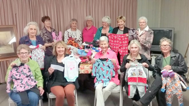 Members of the Ruidoso Federated Woman's Club show off some of the pajamas collected over an extended campaign that were presented to the Nest to be used by victims of domestic violence staying there.