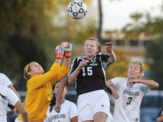 Pittsford Sutherland goalie Morgan Schild, left, reaches to punch a corner kick away from Honeoye Falls-Lima's Riley Bartoo (15).
