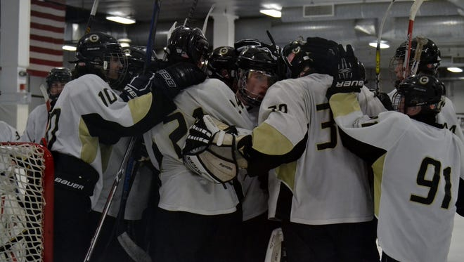 Clarkstown goalie Tim Cavanagh is surrounded by teammates following Sunday's 3-2 win over Rye Town/Harrison at Palisades  Center Ice Rink.
