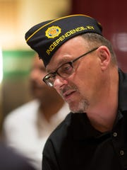 Retired Marine Rusty Mardis of Independence, a manager with the Tristate Veteran Community Alliance, helps a veteran at a job fair at the Hilton Netherland Plaza.