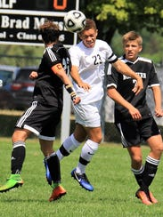 Battling two Walled Lake Northern players for the ball