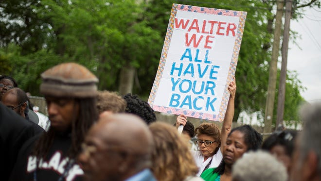 Lisa Eberle, of Charleston, S.C., holds a sign while observing a moment of prayer during a vigil at the scene where Walter Scott was fatally shot by a white police officer after he fled a traffic stop on April 12 in North Charleston, S.C. The officer, Michael Thomas Slager, has been fired and charged with murder.