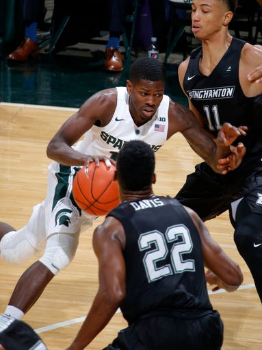 Michigan State's Eron Harris, center, drives against