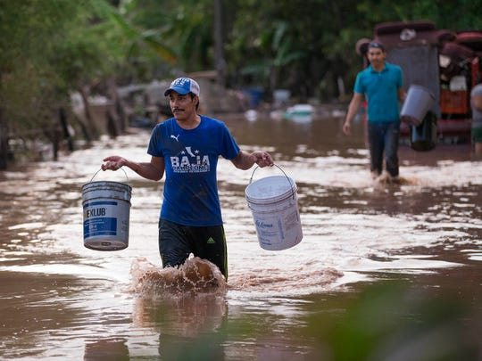 Residents carry buckets on Saturday, October 24, 2015