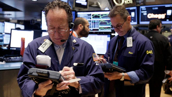 Trader Steven Kaplan, left, works on the floor of the New York Stock Exchange Wednesday. Stocks are getting off to a weak start on Wall Street, following overseas markets lower. (AP Photo/Richard Drew)