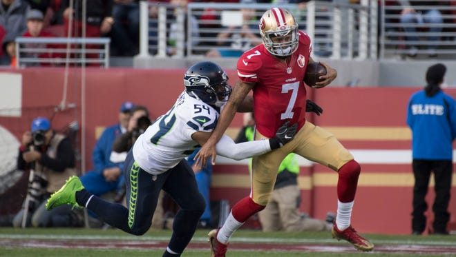 San Francisco 49ers quarterback Colin Kaepernick (7) runs past Seattle Seahawks middle linebacker Bobby Wagner (54) during the second quarter at Levi's Stadium.