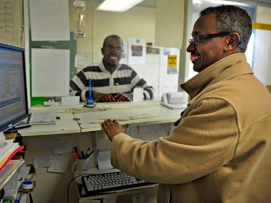Farhan Abdi, right, helps customer Abdirizak Alas send