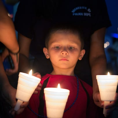A young boy looks down at his lit candle during a candlelight