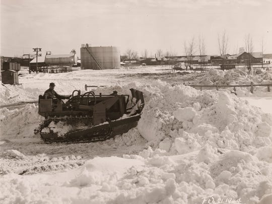 Bulldozer pushes snow at the foot of College Street into Lake Champlain in February 1944.