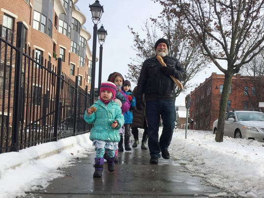 Pre-storm provisions: Burlington resident Stuart Weiss walks down College Street in Burlington with his visiting grandchildren on Sunday afternoon. Front-to-back: Eliana Siegel, 3; Shayna Siegel, 7; and Ethan Siegel, 10. Behind them, not pictured, is their grandmother, Michelle Lefkowitz. Photographed Dec. 24, 2017.