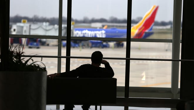 A Southwest Airlines plane waits at a gate as travelers wait in the Civic Plaza at the Indianapolis International Airport.