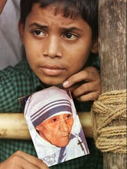 An Indian boy holds a portrait of Mother Teresa as he waits for the return of her procession from the funeral Mass in Netaji Indoor Stadium in Calcutta on Sept. 13, 1997.