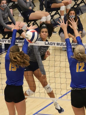 Greenwood's Myia McCoy hits between Mountain Home's Kylee Sabella and Reanna Dodge, in the first set, Tuesday, Sept. 22, at H.B. Stewart Arena.