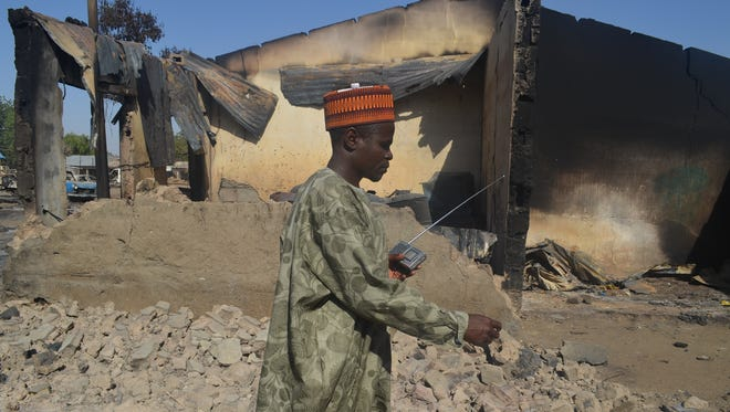 A man walks past a building destroyed in an attack by Boko Haram militants on Feb. 20 in Bama, Nigeria. Boko Haram fighters are suspected in an attack at a college Feb. 25 that left dozens dead.