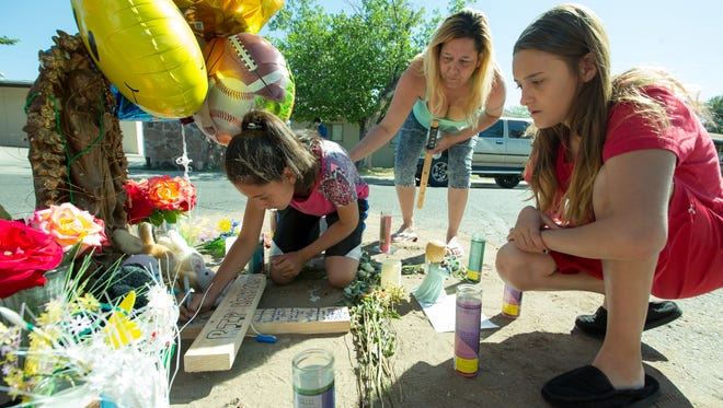 Annissa Mancha, 11, left, Leslie Garcia, center,  and Ranea Garcia, 12, write messages on a cross on Monday, April 17, 2017, at a memorial for 6-year-old Jonah Frausto who was struck by a vehicle Saturday the 700 block of Lees Drive. Jonah died early Sunday morning.