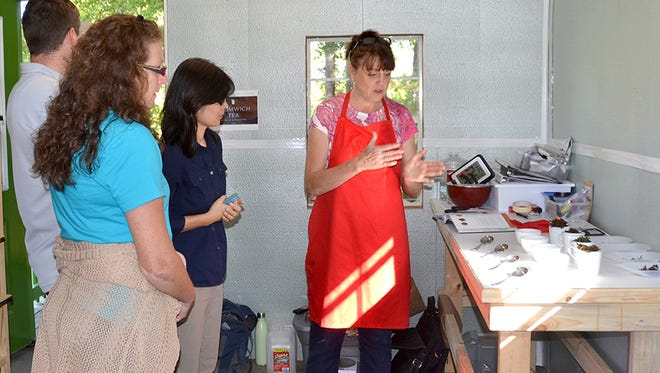 Donna Beliech, horticulture agent with the Mississippi State University Extension Service; Judson Lecompte, MSU research associate, and Guihong Bi, MSU associate research professor, listen as tea blender Beverly Wainwright explains the process of developing tea blends at The Great Mississippi Tea Company in Brookhaven, Mississippi, on Oct. 2, 2015.