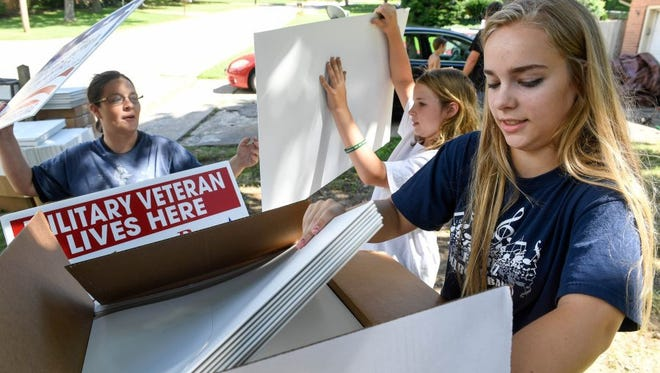 Shawn Gourley (left) with daughters Jesslyn Gourley, 11-years-old, and Jordan Rigdon, 16-years-old, rush to pack the last few veterans fireworks courtesy signs before the mail carrier stops by to pick them up Wednesday. June 29, 2016.