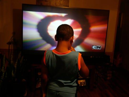 Omar Enrique Vidro Pacheco Jr., 9, watches a cartoon